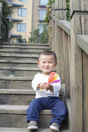 cute babies: Happy Chinese baby boy playing a toy on stairs, shot in Beijing, China Stock Photo