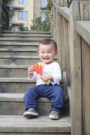 babies playing: Happy Chinese baby boy playing a toy on stairs, shot in Beijing, China Stock Photo
