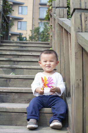 baby cute: Happy Chinese baby boy playing a toy on stairs, shot in Beijing, China Stock Photo