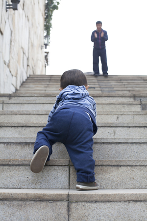 encouraged: Cute Chinese baby boy crawling on stairs, encouraged by his father, real people