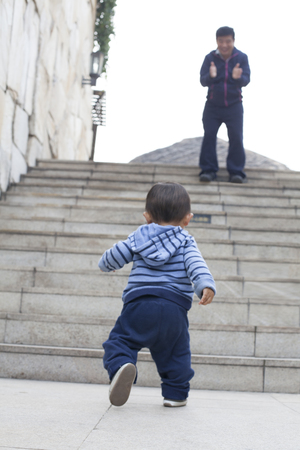 encouraged: Cute Chinese baby boy learning walking, encouraged by his father, real people