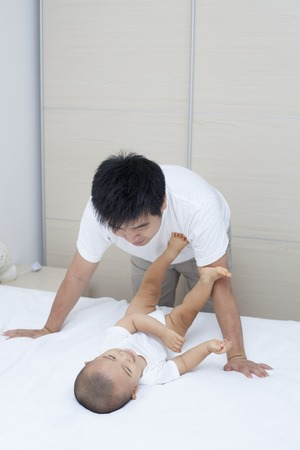 baby wardrobe: Tender moment between Chinese father and son, real people, shot in Beijing, China Stock Photo