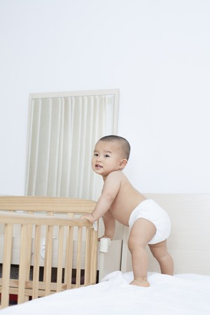 Cute Chinese baby boy standing by his Crib, shot in Beijing, China Stock Photo