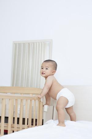 Leuke Chinese baby boy staan door zijn Crib, schoot in Beijing, China