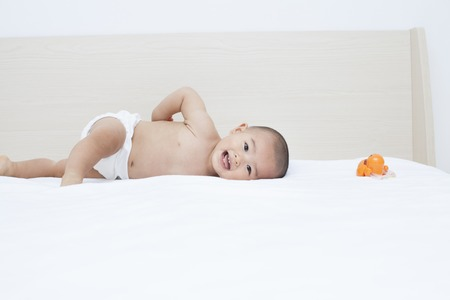 happy baby: Cute Chinese baby boy lying in bed, shot in Beijing, China