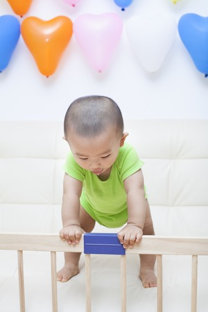 baby boy: Chinese baby boy playing on a sofa, shot in Beijing, China