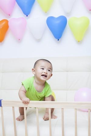 bebes lindos: Beb� chino que juega en un sof�, un disparo en Beijing, China Foto de archivo