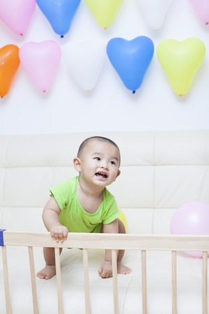 cute babies: Chinese baby boy playing on a sofa, shot in Beijing, China