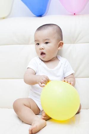 baby sit: Chinese baby boy and colorful balloons, shot in Beijing, China Stock Photo