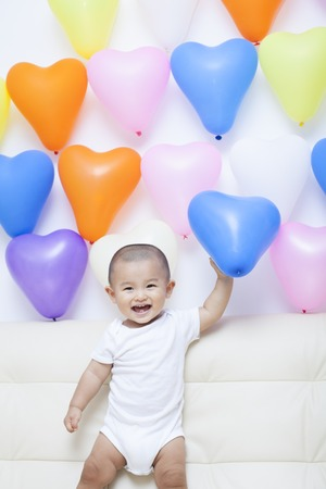 cute babies: Chinese baby boy and colorful balloons, shot in Beijing, China Stock Photo