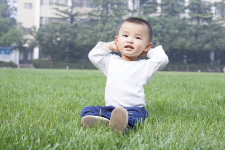 cute boys: Cute Chinese baby boy sitting on meadow Stock Photo