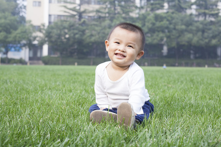 boy sitting: Cute Chinese baby boy sitting on meadow Stock Photo