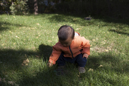 blow hole: Cute Chinese baby boy studying a fountain blow hole in grass, shot in Beijing, China Stock Photo