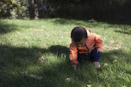 12 18 months: Cute Chinese baby boy studying a fountain blow hole in grass, shot in Beijing, China Stock Photo