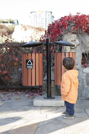 12 18 months: Chinese baby boy looking at a Garbage Bin, shot in Beijing, China