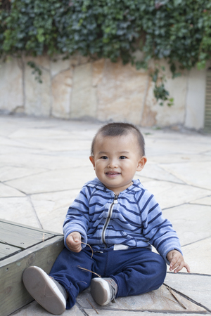 cute boys: Cute Chinese baby boy playing outdoors, shot in Beijing, China Stock Photo