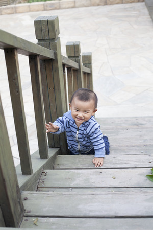 12 18 months: Cute Chinese baby boy crawling on stairs, shot in Beijing, China
