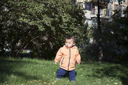 12 18 months: Cute Chinese baby boy playing outdoors, shot in Beijing, China Stock Photo