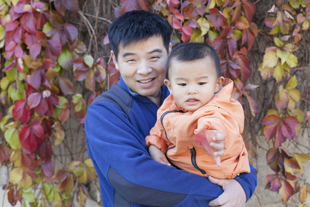 cute man: Happy Chinese father and son in front of Boston Ivy, shot in Beijing, China Stock Photo