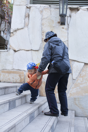 60 65 years: Chinese grandmother helping grandson walking on stairs, shot in Beijing, China