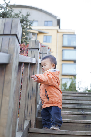 12 18 months: Happy Chinese baby boy playing on stairs outdoors, shot in Beijing, China