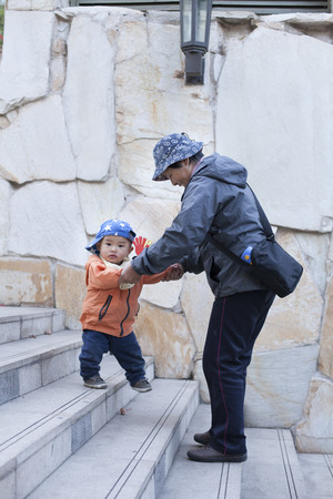 12 18 months: Chinese grandmother helping grandson walking on stairs, shot in Beijing, China