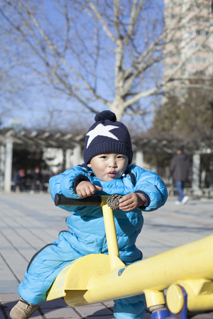 12 18 months: Cute Chinese baby boy playing seesaw outdoors, shot in Beijing, China
