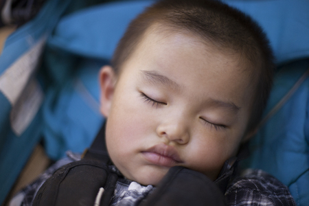 baby stroller: Cute Chinese baby boy in sleep in a baby stroller, shot in Beijing, China Stock Photo