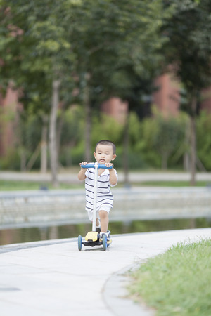 Happy Chinese baby boy playing a scooter, shot in Beijing, China Stock Photo
