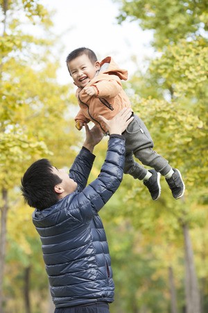 Happy real father and son playing in front of ginkgo trees, shot in Beijing, China Stock Photo