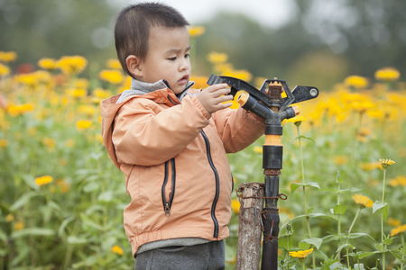 Cute baby boy playing a faucet in blossoms, shot in Beijing, China