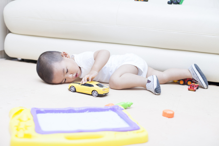 Cute Chinese baby boy playing a toy car indoors, Shot in Beijing,China