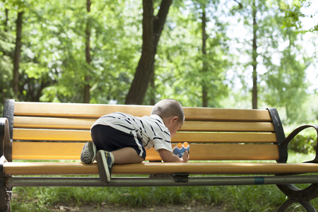 Cute Chinese baby boy playing on a bench in woods, Beijing, China