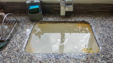Fregadero de la cocina desbordado, desagüe obstruido. Foto de archivo