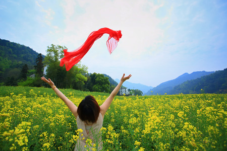 letting: Woman let go of her red scarf over the meadow