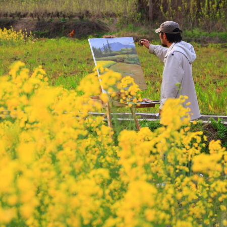 man painting: Man painting by a plantation field