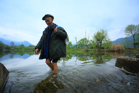 carrying the cross: Old man crossing the river Editorial