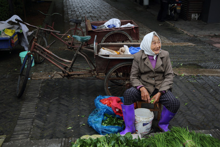 one senior woman only: Elderly woman selling vegetables
