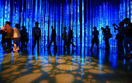 25 30 years women: Crowd walking in dark hall with neon lights