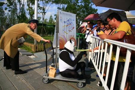 interacting: Man in panda costume interacting with tourist