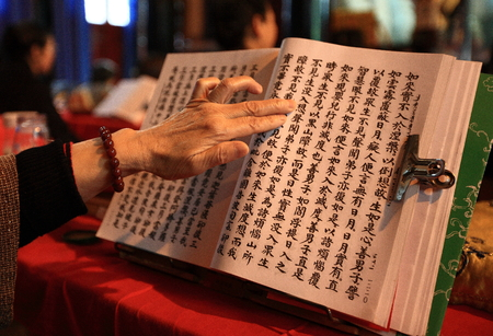 sutra: Woman holding a page of chinese sutra Editorial