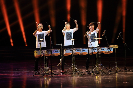 performing: Three men performing with drums on stage