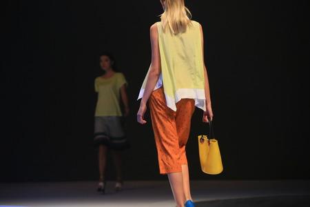 facing to camera: A young woman holding a handbag with her back facing camera