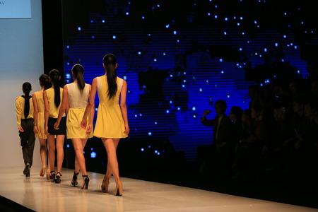 facing to camera: Five models on catwalk runway back facing camera