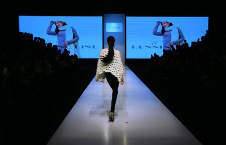 facing to camera: A model walking on catwalk runway with back facing camera