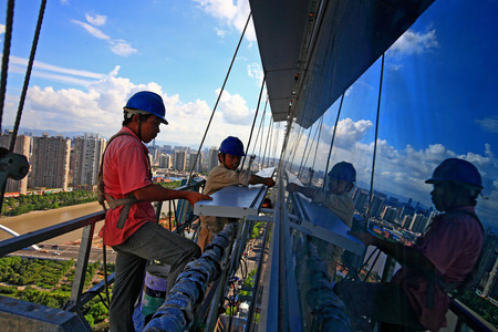 4s: Two construction workers working on a building's window