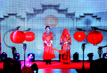 attire: Bride and bridegroom in traditional attire on stage Editorial