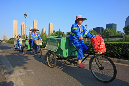 only three people: Three workers cycling tricycles