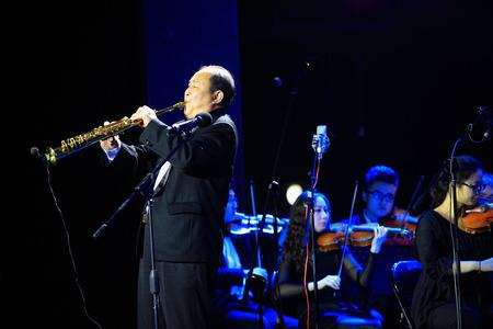clarinete: Hombre con clarinete en el escenario con la orquesta Editorial