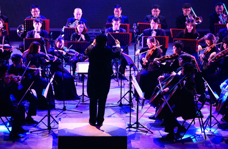 maestro: Conductor conducting orchestra on stage
